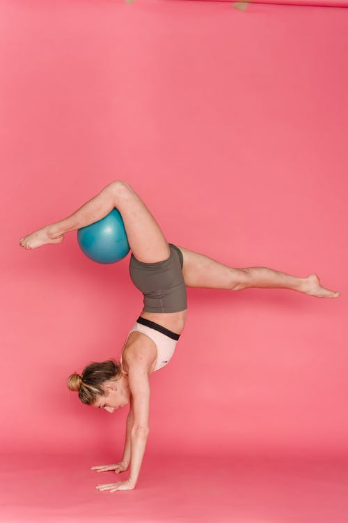 Slim woman doing balance exercise during practice with fitness ball