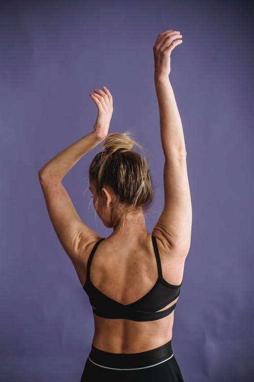 Slim woman raising arms for recovering after workout