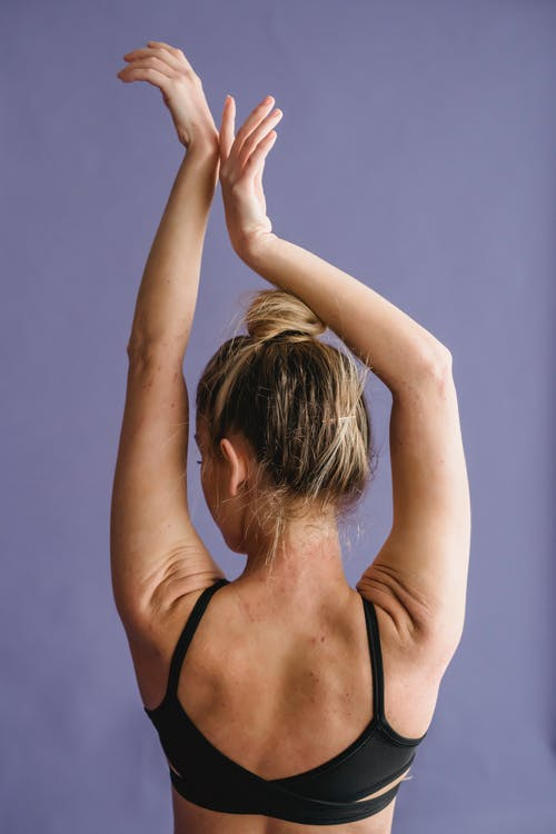 Back view of unrecognizable female athlete stretching arms up while recovering after training against violet background