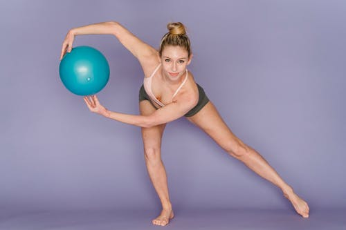 Full body of positive young female athlete wearing sportswear outstretching leg and bending forward during training with fitness ball