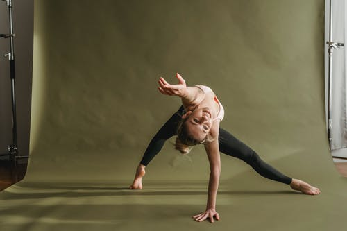 Sporty woman outstretching hand while practicing dance