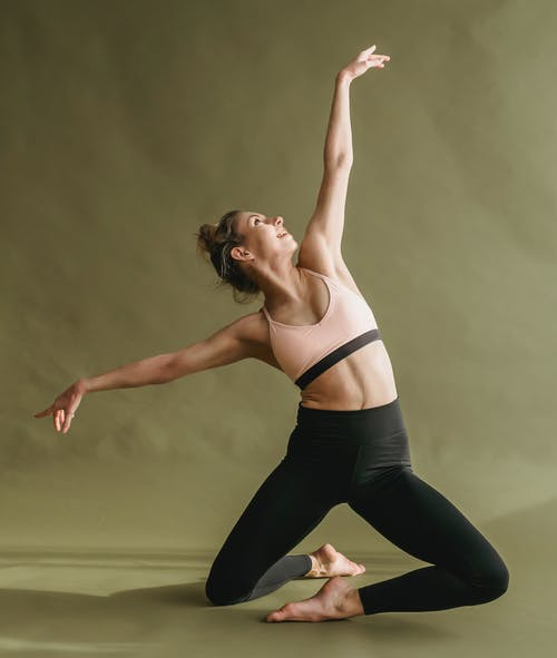 Full body of smiling female dancer wearing activewear outstretching arms while performing graceful dance and looking away