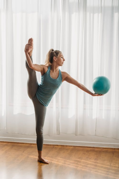 Woman in Blue Tank Top and Black Leggings Holding Blue Ball