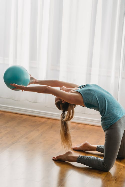 Slender young woman training with gymnastic ball in studio