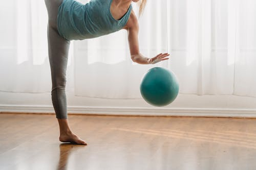 Woman in Blue Tank Top and Gray Leggings Holding Blue Exercise Ball
