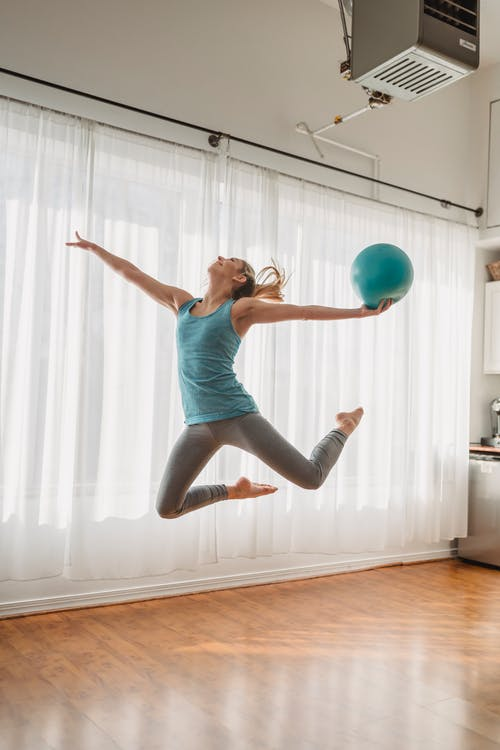Woman in Blue Tank Top and Black Leggings Jumping on White Window Curtain