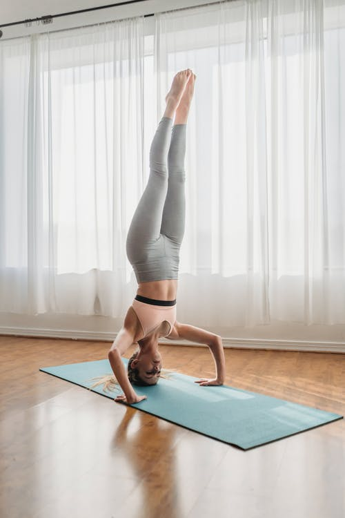Woman in Black Tank Top and Leggings Doing Yoga