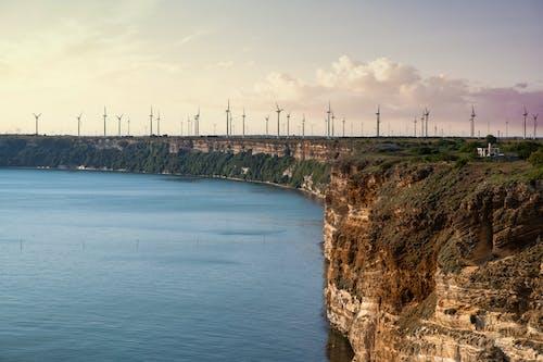 Cape with windmills near calm sea