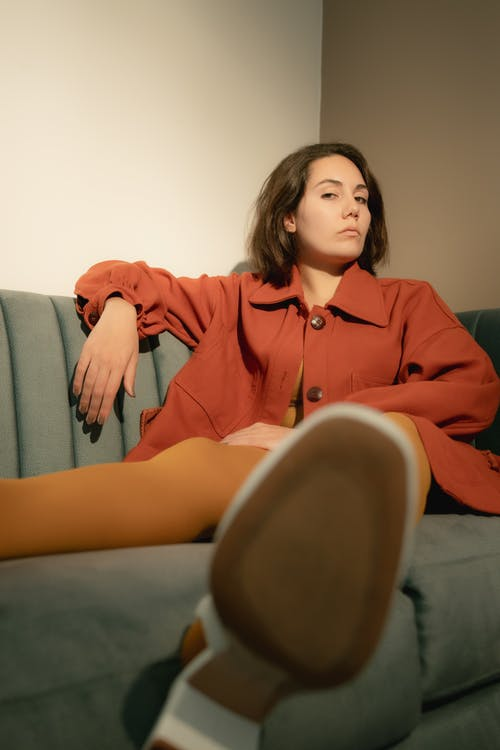 Woman in Red Coat Sitting on Green Couch