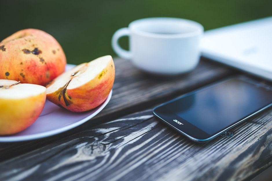 Mobile phone, apple, coffee on the wooden table