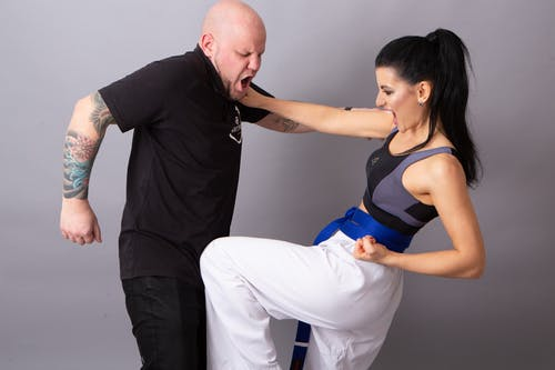 Strong sportswoman with partner performing self defense technique during combat