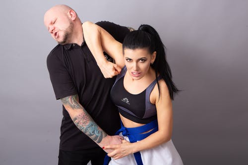 Young rebellious female karateka with tattooed man demonstrating elbow kick during self defense fight on gray background