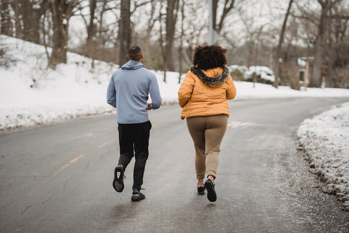 Back view full length fit male fitness trainer and plump female in warm jacket jogging together on asphalt roadway in snowy forested suburb on cold winter weather