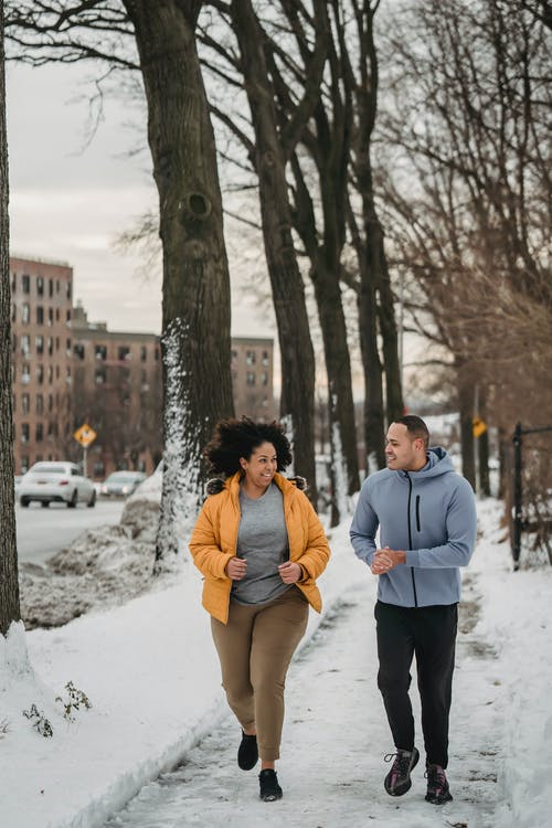 Cheerful trainer and black woman running in winter city park