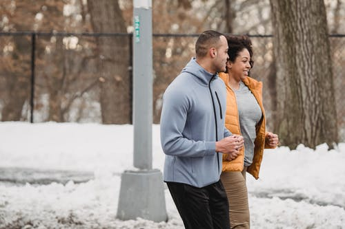 Ethnic man and woman jogging together on winter street