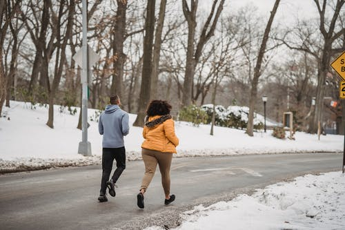 Back view anonymous fit male trainer and plus sized female with curly hair wearing warm clothes jogging together on roadway in snowy winter suburb