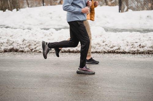 Crop unrecognizable sportspeople jogging on snowy roadway