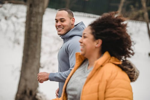 Happy ethnic man and woman jogging on snowy street