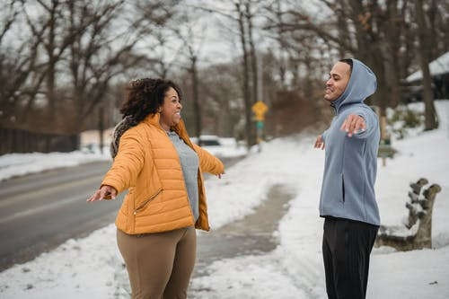 Side view happy ethnic fit male trainer and plump black female in warm clothes performing side arms raise exercise while warming up on snowy winter sidewalk