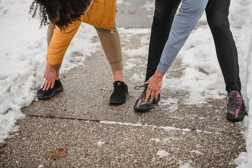 Crop faceless sportspeople doing windmill arm exercise on snowy sidewalk