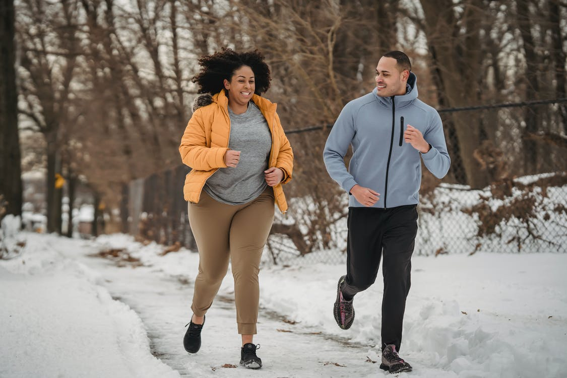 Full length smiling ethnic male fitness trainer and plus sized black female in warm jacket jogging together on snowy pathway in frozen winter park