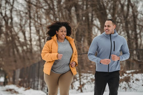 Cheerful multiethnic man and woman running together in winter park