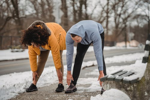 Full length anonymous fit male fitness trainer and plump trainer bending down while stretching body on snowy sidewalk in winter park
