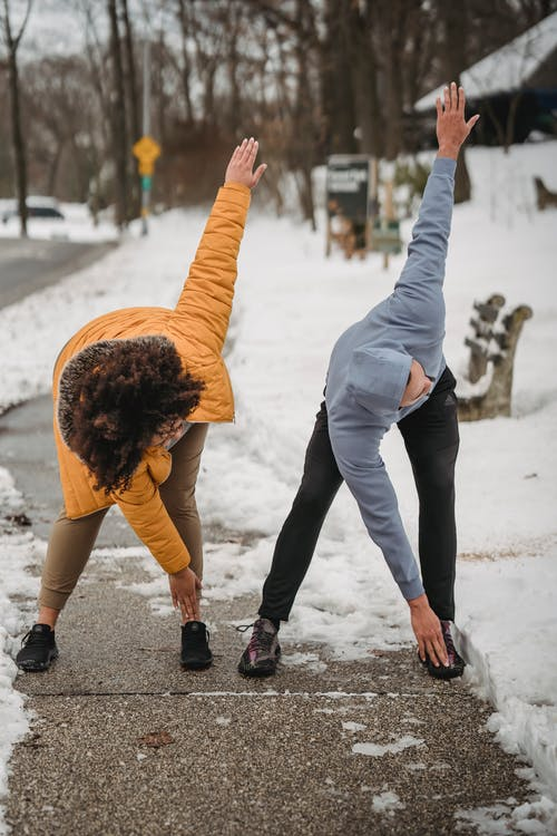 Faceless sportspeople doing windmill arms exercise on snowy street