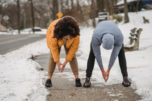 Full length faceless ethnic male trainer and plump female stretching body and bending down before working out on snowy sidewalk on winter day