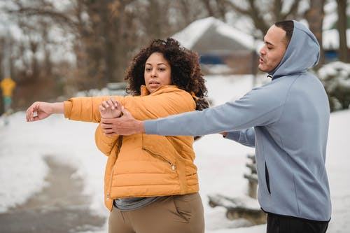 Trainer teaching plump female to stretch triceps in winter suburb