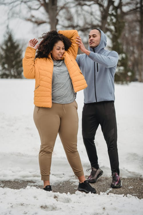 Full length professional ethnic male trainer in activewear helping plus sized black female to stretch arm behind head while working out in snowy winter park