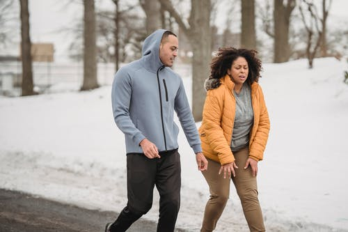 Exhausted plump African American female in outerwear with black personal instructor on pathway in snowy park during training in winter time