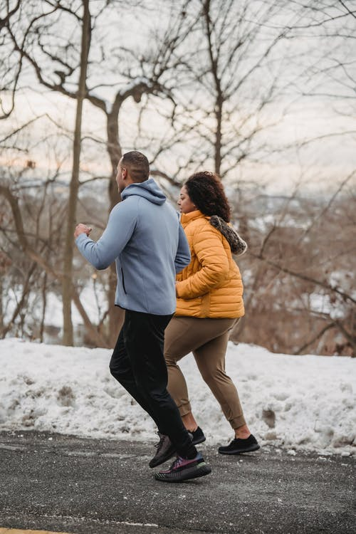 Full body side view of African American male instructor running with plus size black female on sidewalk in winter time
