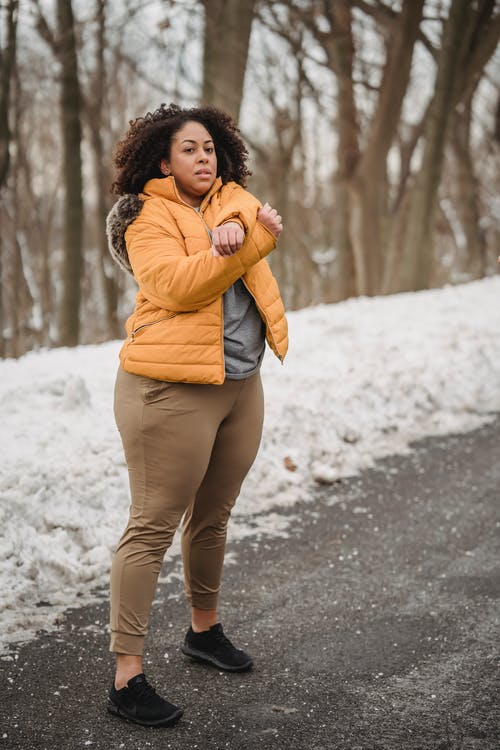 Full body of focused plus size African American female in warm clothes warming up on asphalt walkway in snowy park before training