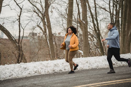 Full body of plus size African American female running with personal instructor on asphalt road during winter training on street