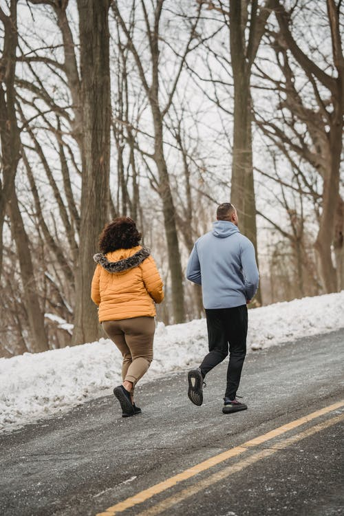 Unrecognizable couple running in snowy park