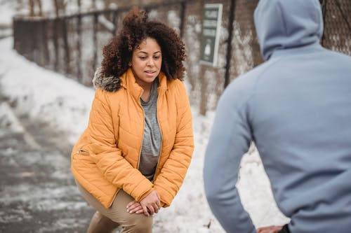 Serious black woman warming up with anonymous trainer in snowy park
