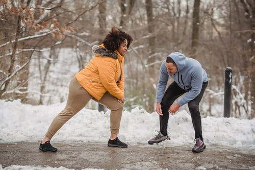 Young trainer controlling black woman in doing lunges