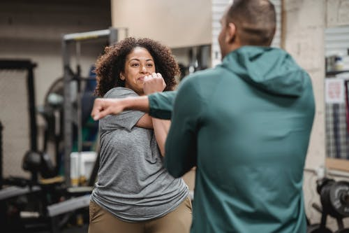 Trainer warming up with black woman in gym