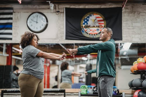 Side view of focused African American female and experienced instructor stretching hands in gym