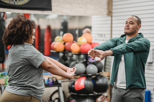 Black woman warming up with trainer in gym