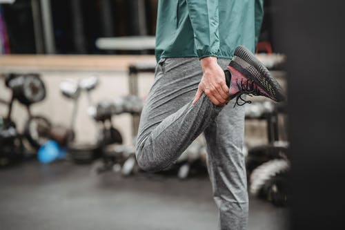 Man in activewear stretching legs in gym