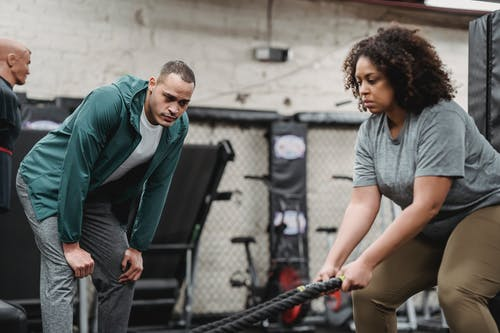 Pensive professional instructor supporting concentrated plump African American woman in training with gym equipment