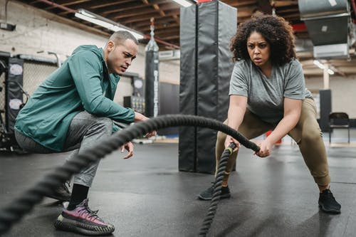 Full body determined African American female in activewear exercising with battling ropes near serious male fitness instructor in contemporary sports club