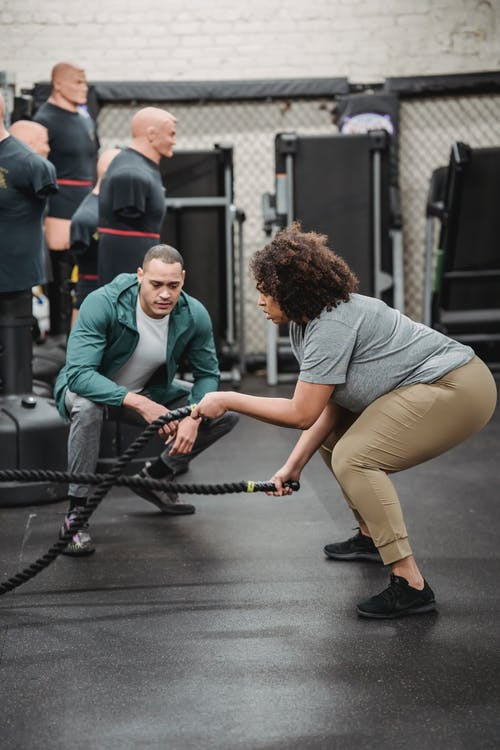 Plus sized ethnic woman exercising with battle ropes in gym