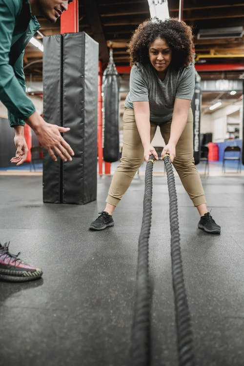Positive plus sized African American female in sportswear with battle ropes listening to professional male trainer instructions in gym
