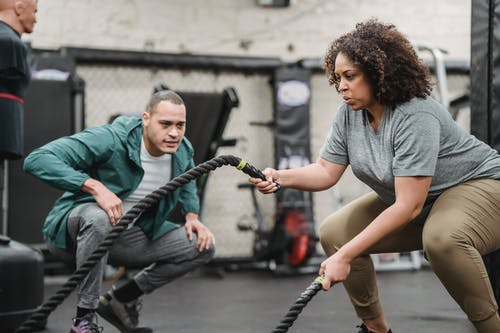 Determined black plump woman exercising with battle ropes in gym