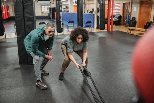 Full body black female in sportswear exercising with battle ropes near professional male instructor in modern gym