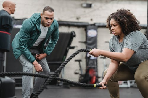 Plus sized African American female in sportswear exercising with battle ropes near serious male instructor during intense workout in modern fitness center