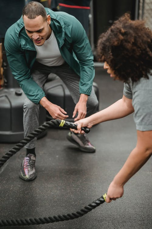 Sporty male coach training woman with battle ropes